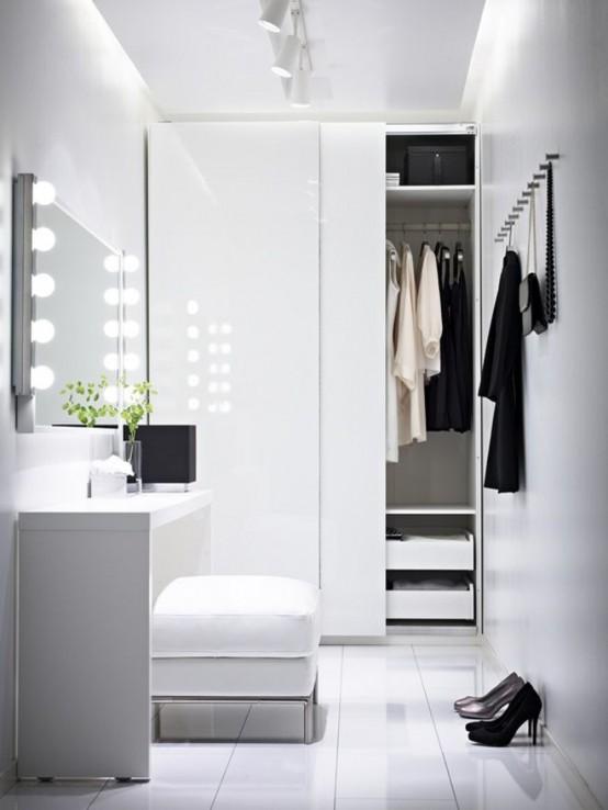 witte minimalistische kledingkast met hoogglans deuren en klein bureau voor spiegel
