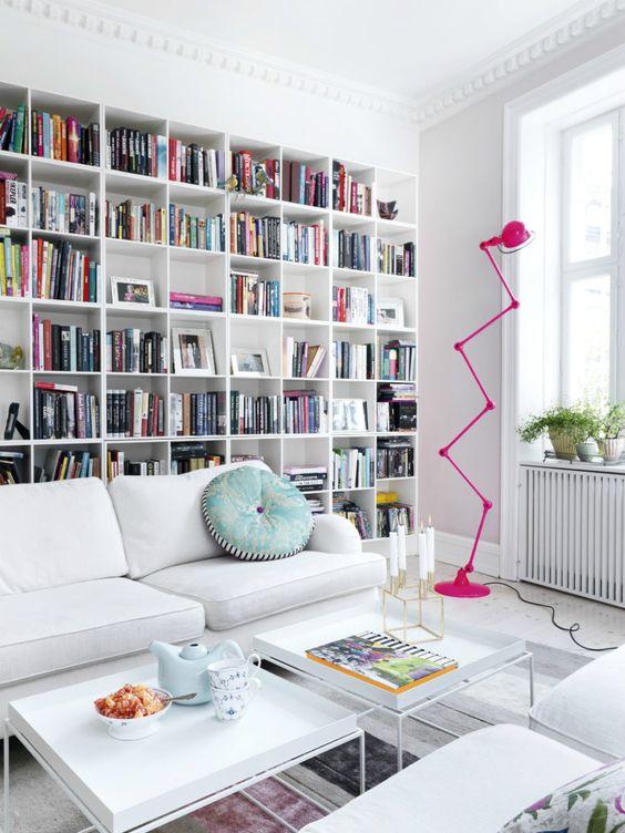 witte woonkamer met grote kastenwand vol boeken